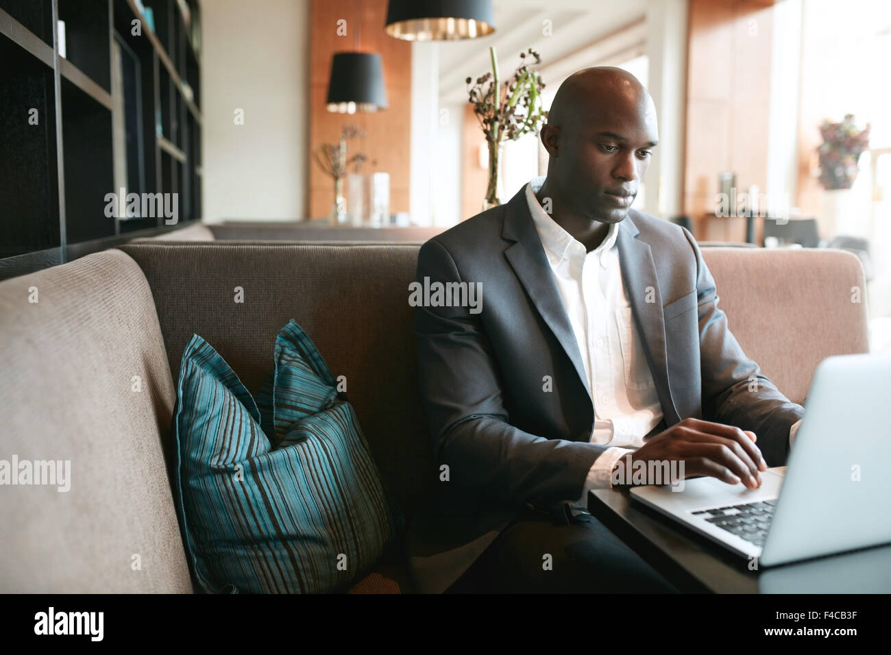 Image of young man sitting at cafe working on laptop. African businessman at coffee shop surfing internet on laptop. - Stock Image