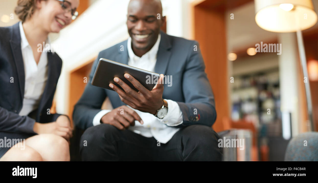 Happy young business people sitting together using digital tablet while at hotel lobby. Focus on tablet computer. - Stock Image