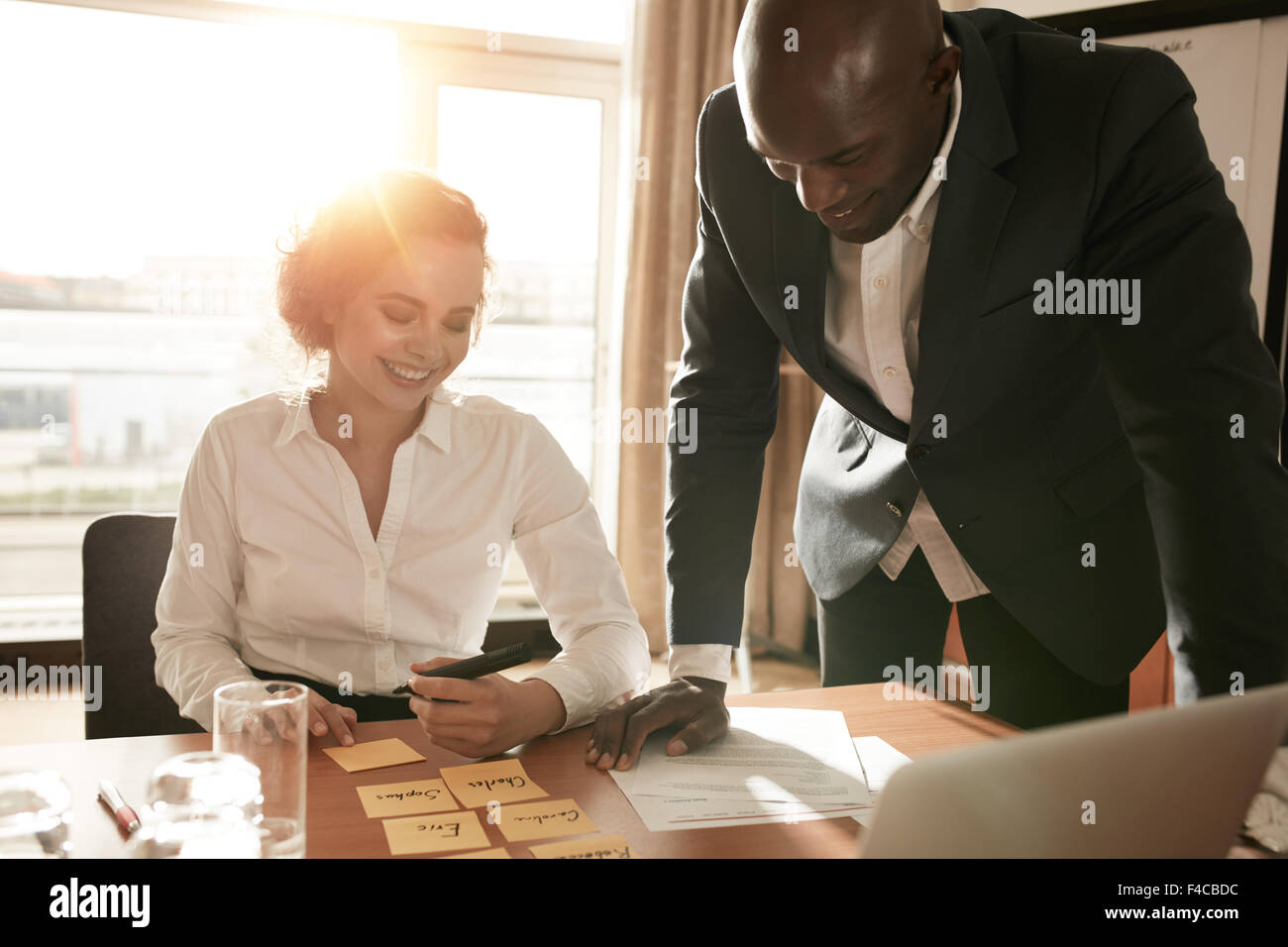Young business colleagues in conference room discussing manpower resources. Businesswoman sitting with names on - Stock Image