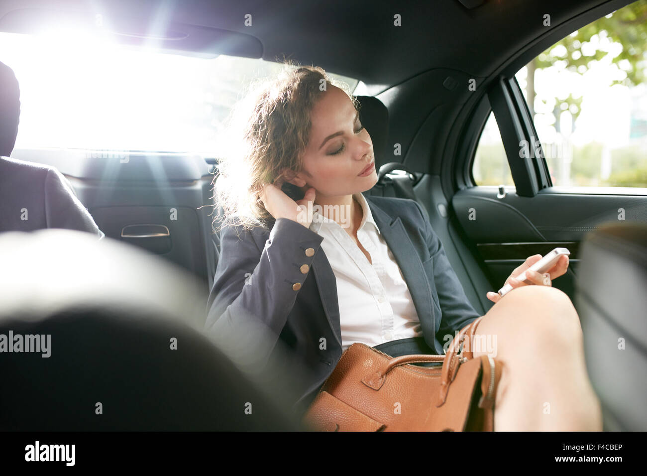 Inside shot of a car with woman sitting with her eyes closed on backseat. Female entrepreneur travelling to work - Stock Image
