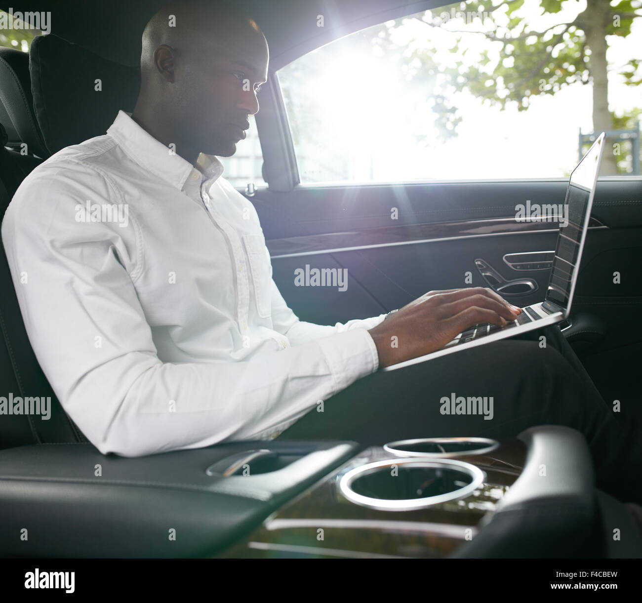 Shot of young african businessman working on laptop inside a car. Business associate travelling to work in a car. - Stock Image