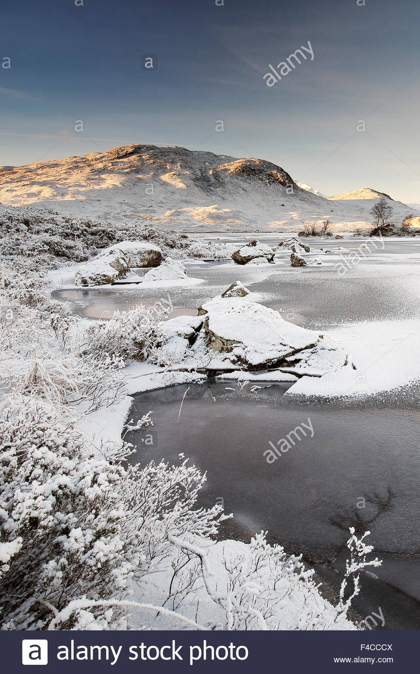 A frozen Loch and snow capped covered mountains in the Scottish highlands. - Stock Image