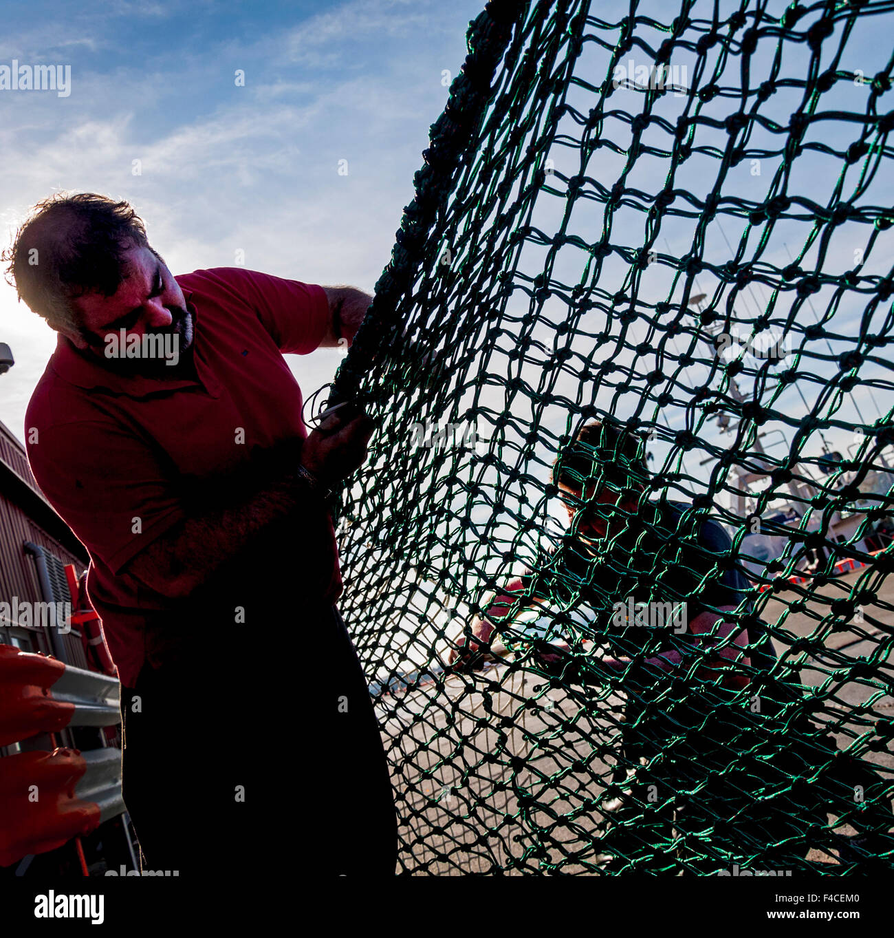 Killybegs, County Donegal, Ireland. October 16th 2015. Fishermen repairing nets on the dockside of Ireland's - Stock Image