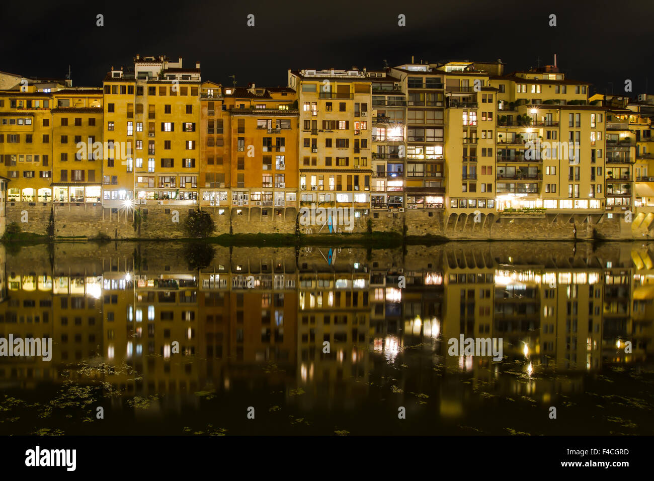 Old houses and tower on the embankment of the River Arno and Ponte Vecchio at night, Florence, Tuscany, Italy - Stock Image