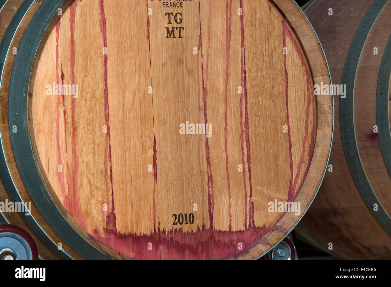 China, Ningxia. Red wine stains the end of an oak barrel at Helan Mountain winery. - Stock Image