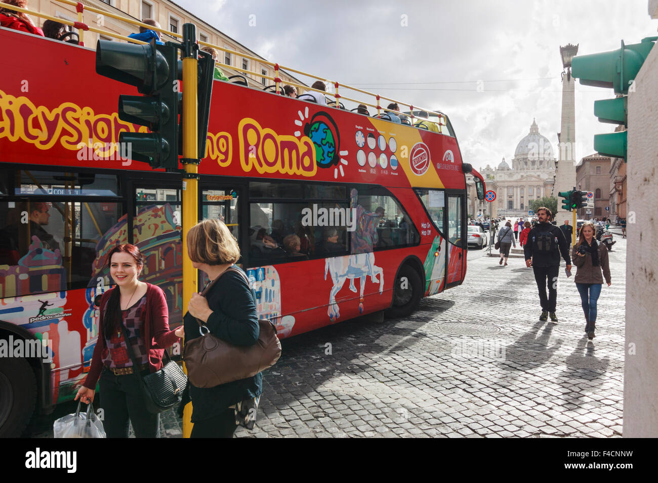 Two women next to a sightseeing bus at Vatican city, Rome, Italy - Stock Image
