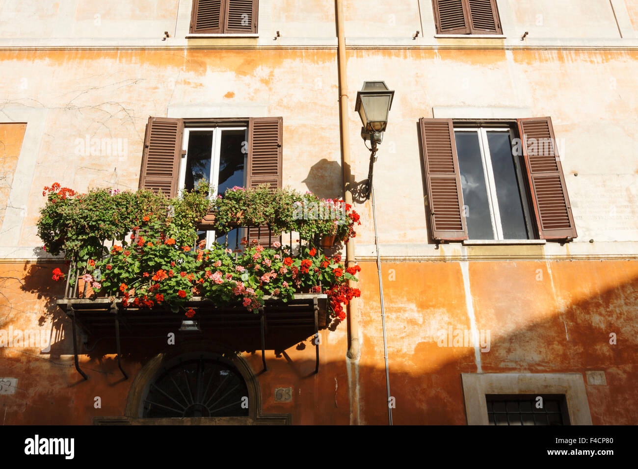 Ochre walls in warm tones characterize the roman urban landscape. Via Giulia, Rome, Italy - Stock Image