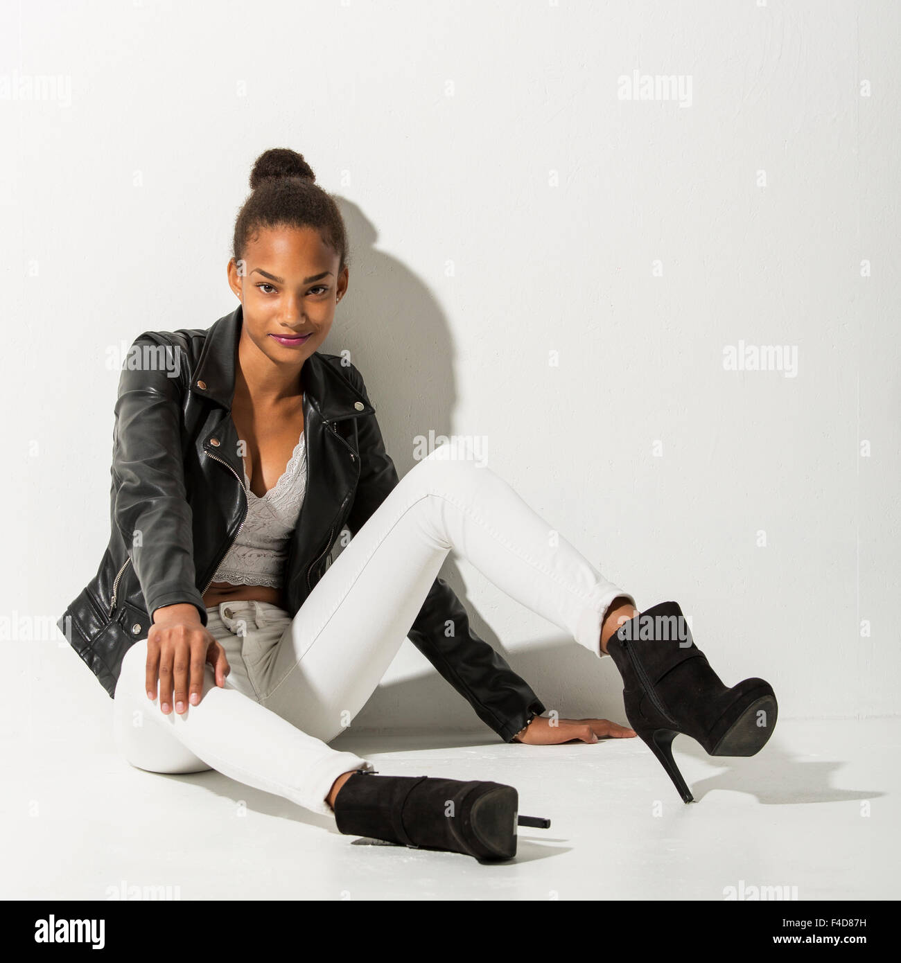Teenage fashion model sitting on a white floor leaning towards a white wall. She is looking into the camera with - Stock Image