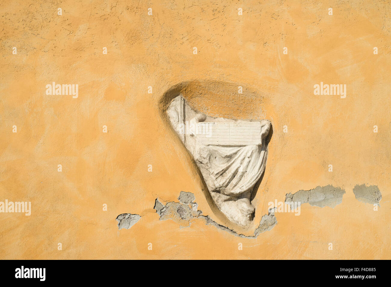Ancient Roman sculpture fragment stuffed on a wall in Via Francesco Mengotti, Rome, Italy - Stock Image