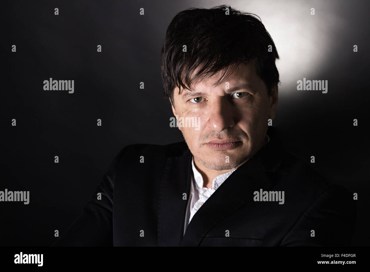 Handsome man in his 40's looking in the camera with a serious attitude. Wearing white shirt and a black jacket. Stock Photo