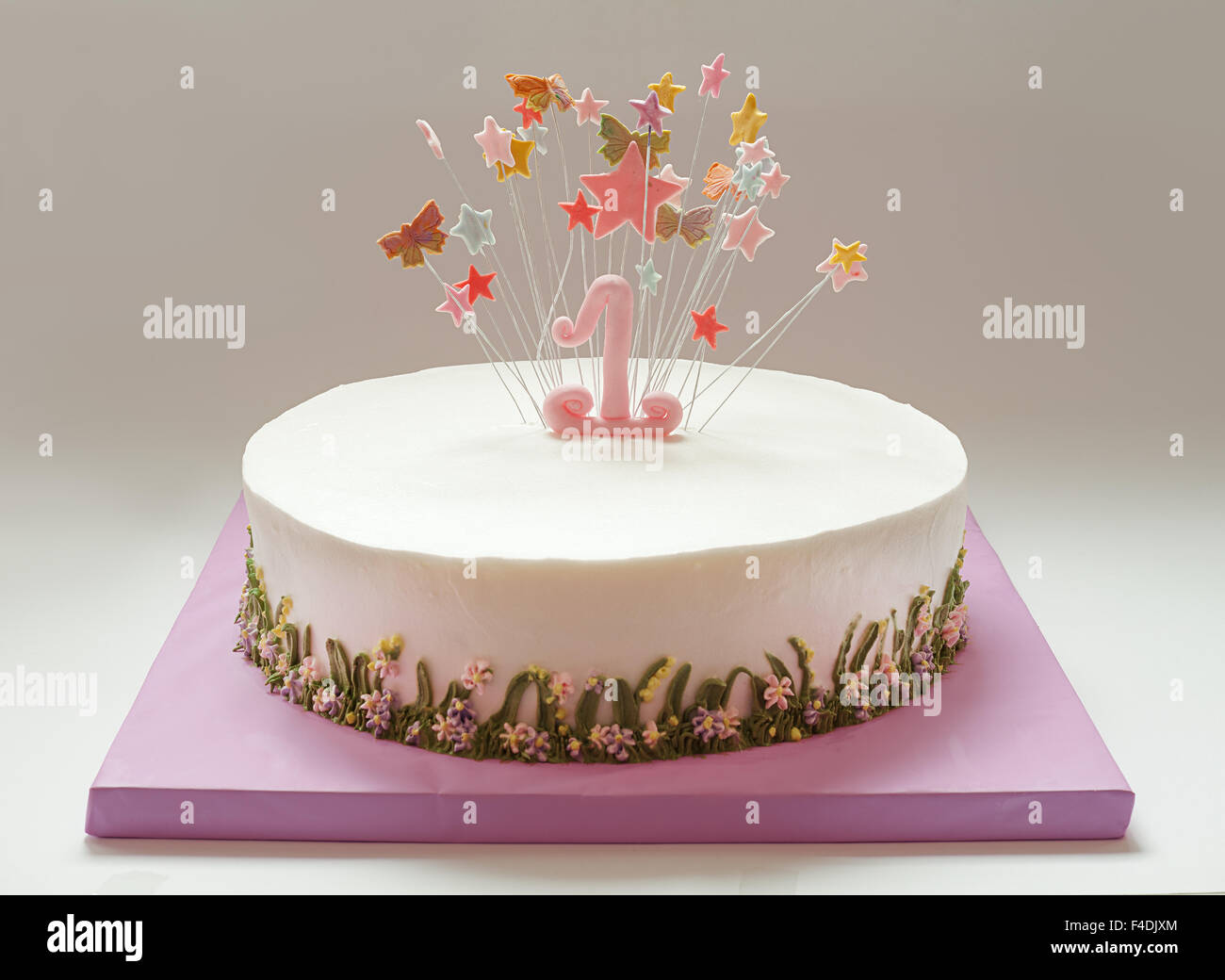 Birthday cake with number one and stars on top. - Stock Image