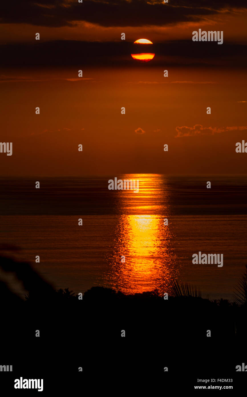 Sunset with reflections on the water viewed from Dili, East Timor - Stock Image