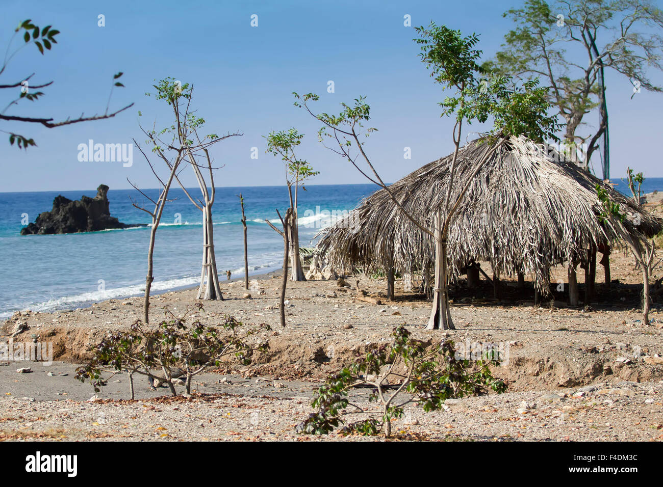 Tropical beach in East Timor and an empty hut to provide shadows - Stock Image