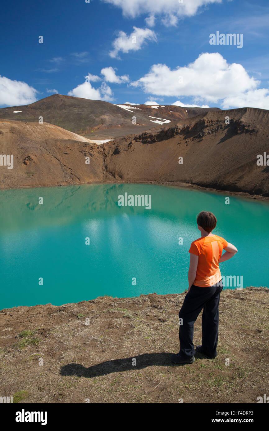 Visitor admiring Viti crater, Krafla volcanic area, Myvatn, Nordhurland Eystra, Iceland. - Stock Image