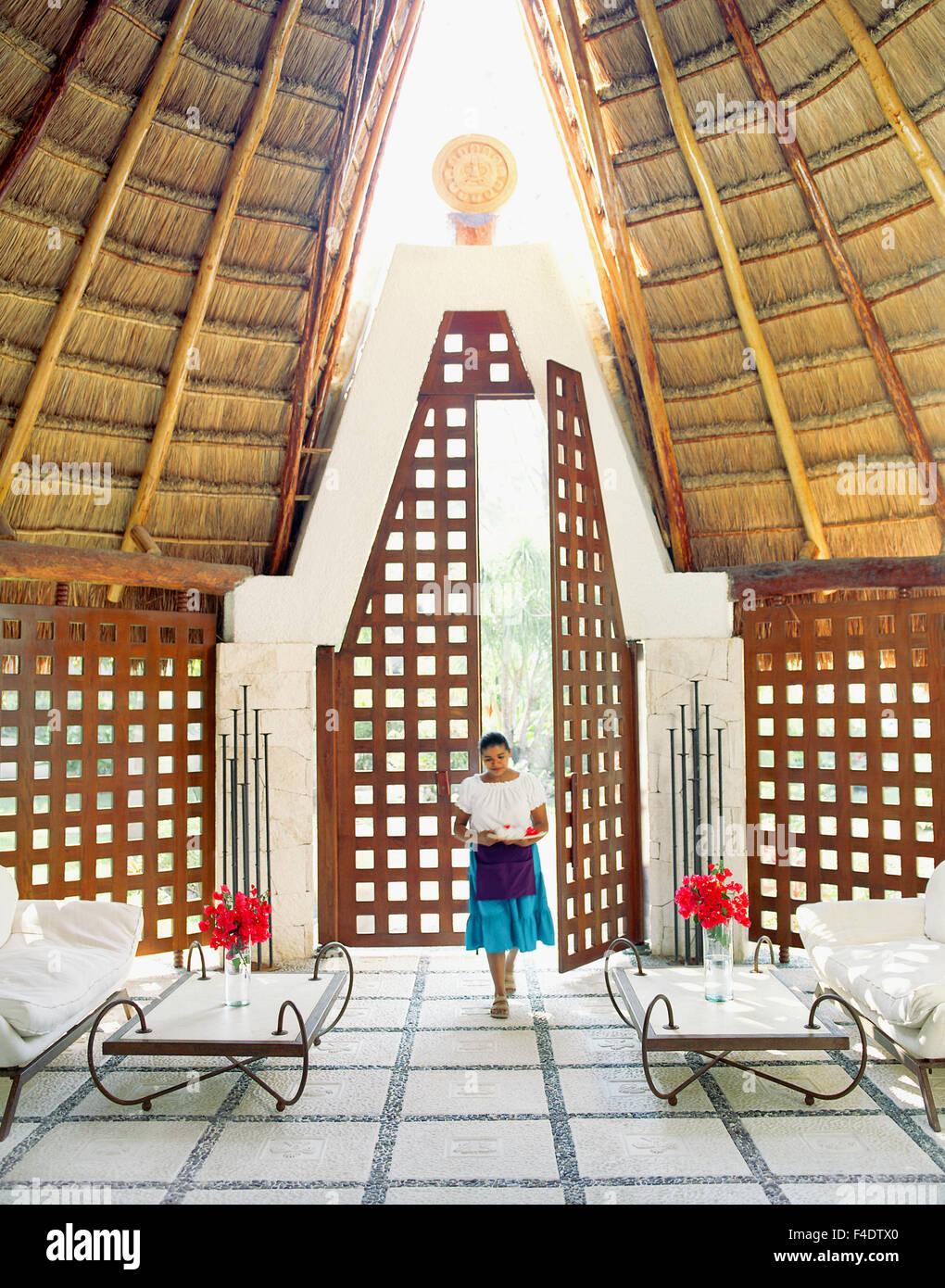 A Mexican staff member walks through the main spa entrance at Maroma Spa and Resort. Riviera Maya,Yucatan,Mexico. - Stock Image