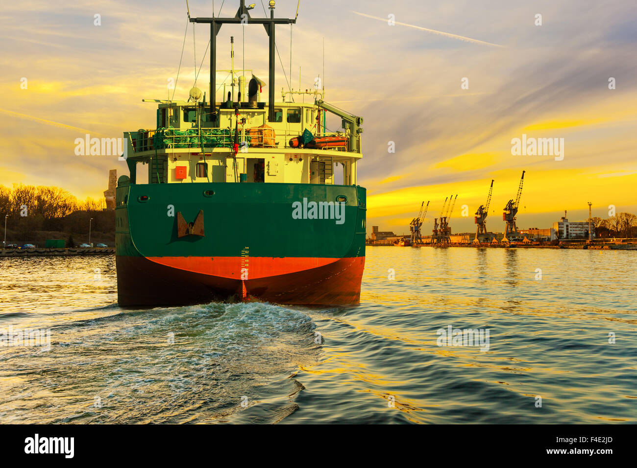 Cargo ship at sunset coming to port. - Stock Image