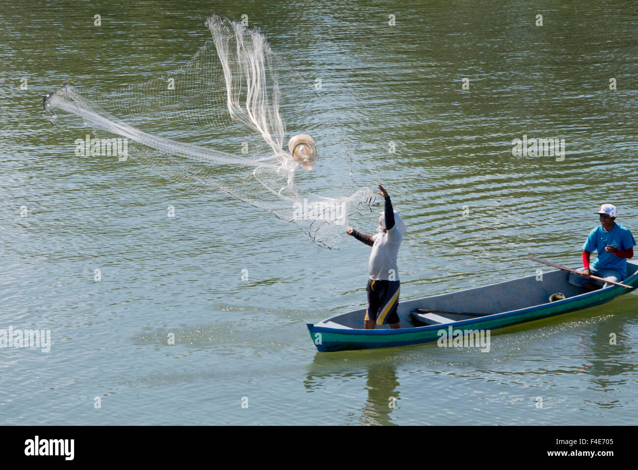 Guatemala, Izabal, Rio Dulce (Sweet Water River) near Livingston. Traditional fishermen in wooden boat tossing net Stock Photo