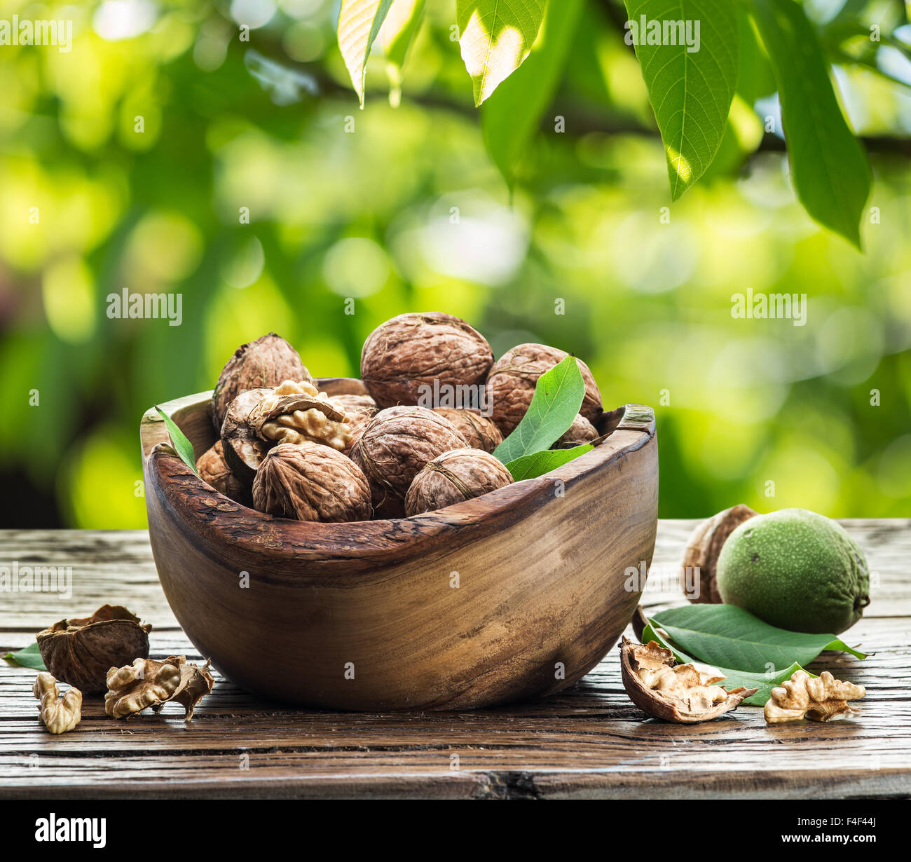 Walnuts in the wooden bowl on the table. The bright nature background. - Stock Image