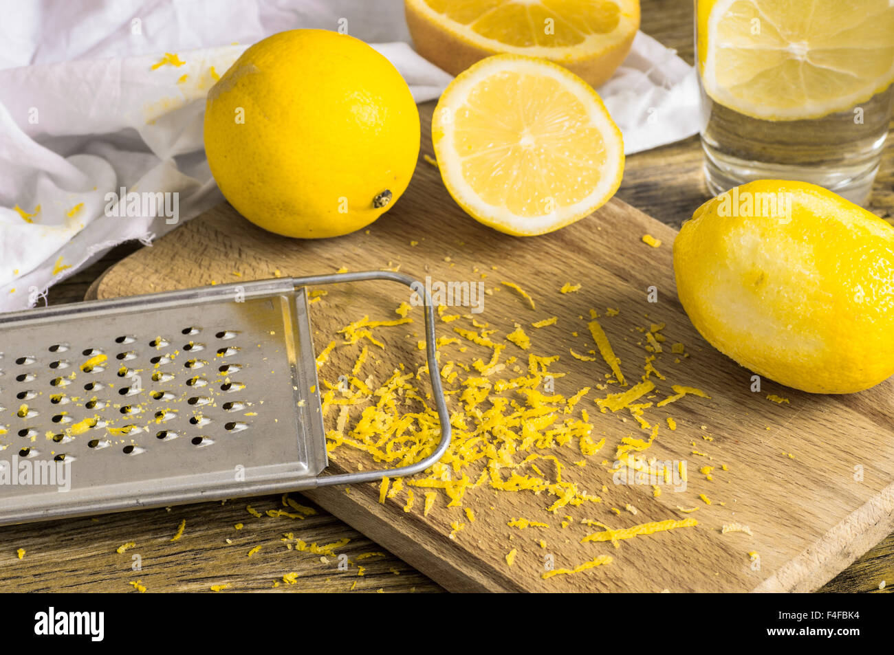 Grater peel and lemon zest on the wooden table - Stock Image