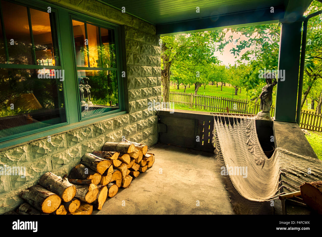 USA, Washington, Klickitat. Country cottage in wine country offers hammock on the porch with view of orchard and - Stock Image