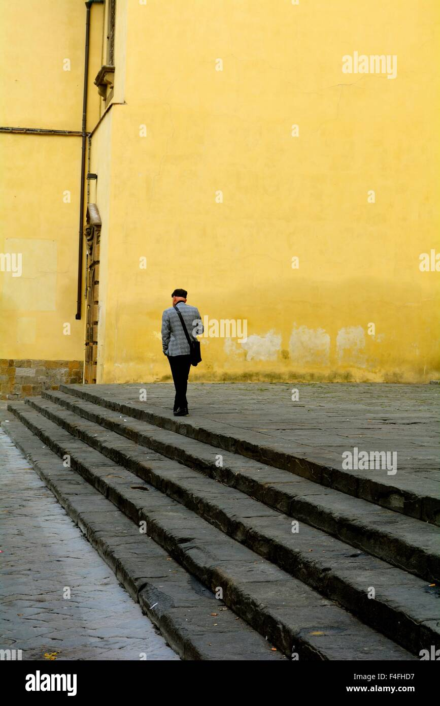 Man walking along steps next to a yellow wall in Oltrarno, Florence ...