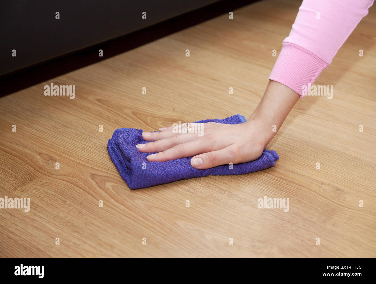 woman's hand cleaning the wooden floor with a blue floorcloth closeup - Stock Image