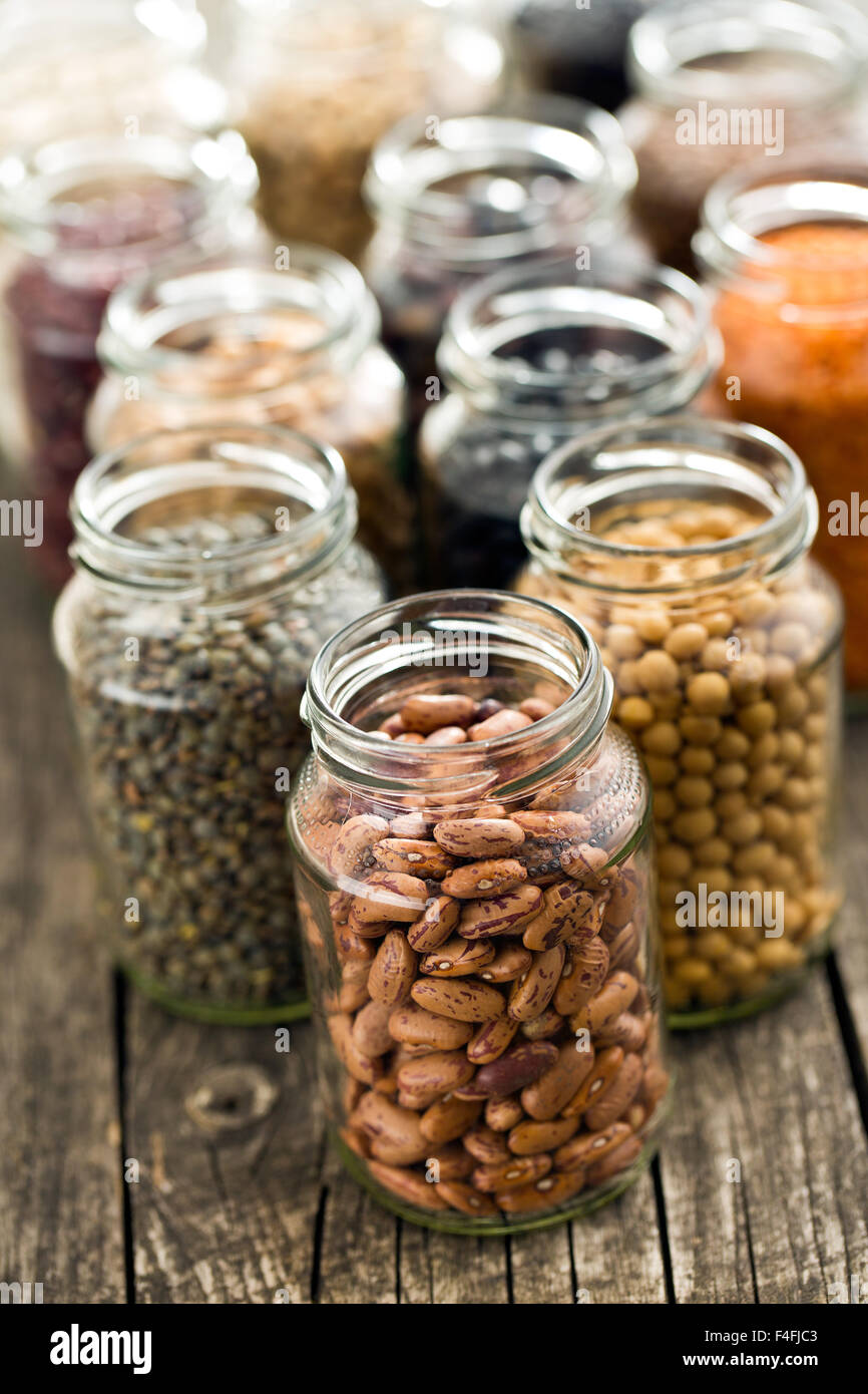 various dried legumes in jars on old table - Stock Image