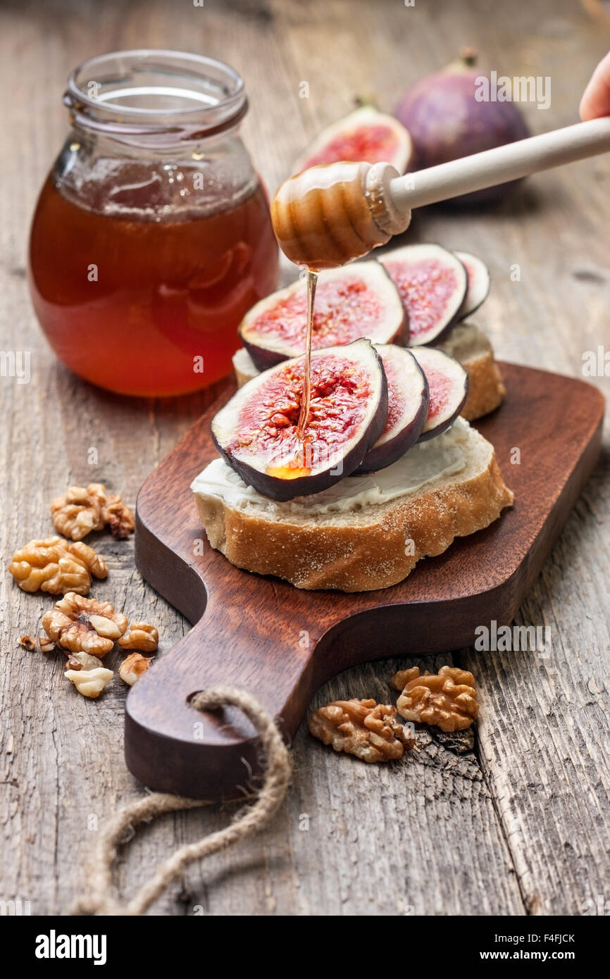 bread with figs, ricotta, honey, walnut  on a cutting board - Stock Image