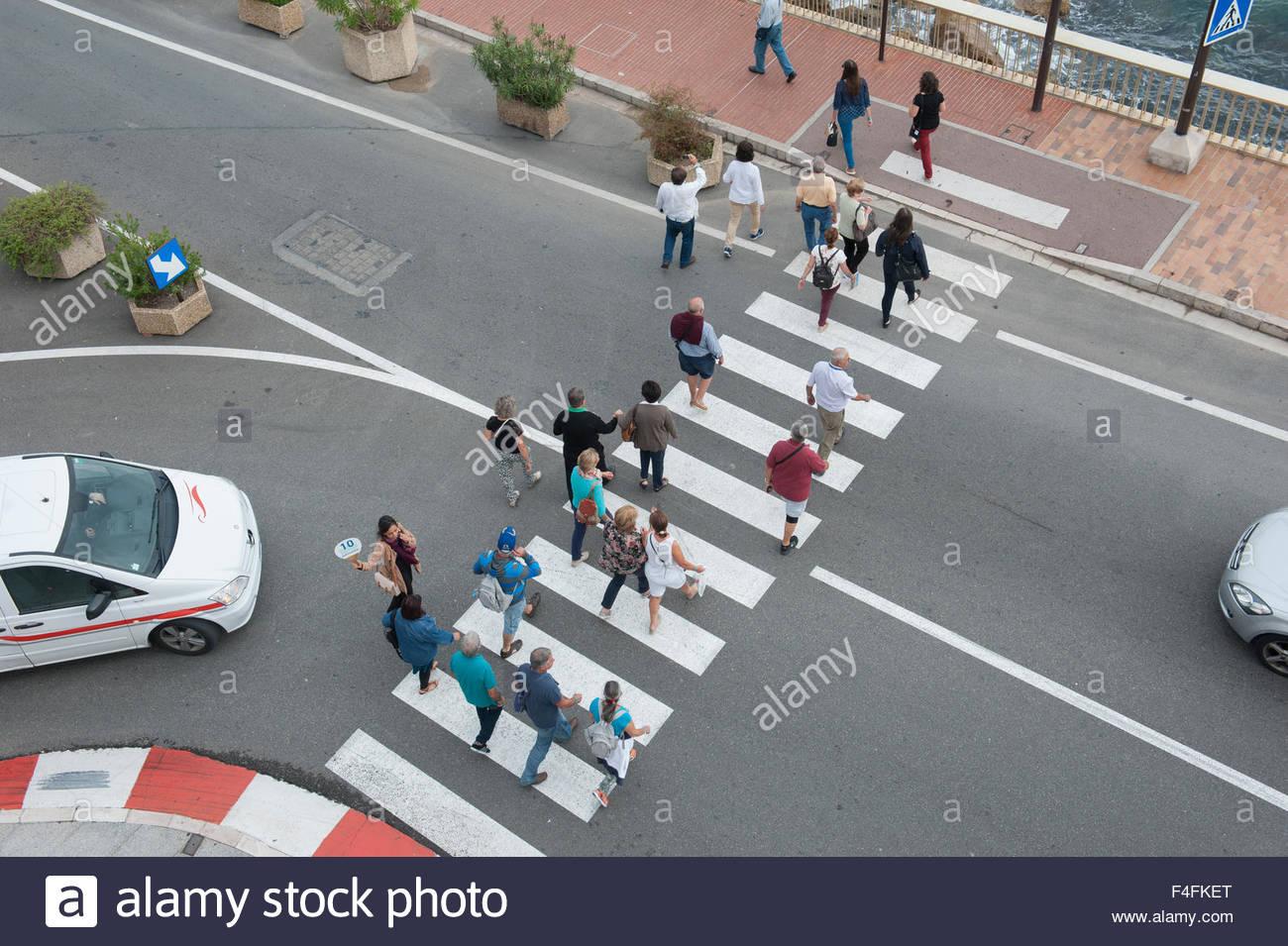 Monte Carlo Monaco Tourists cross a zebra crossing. Stock Photo