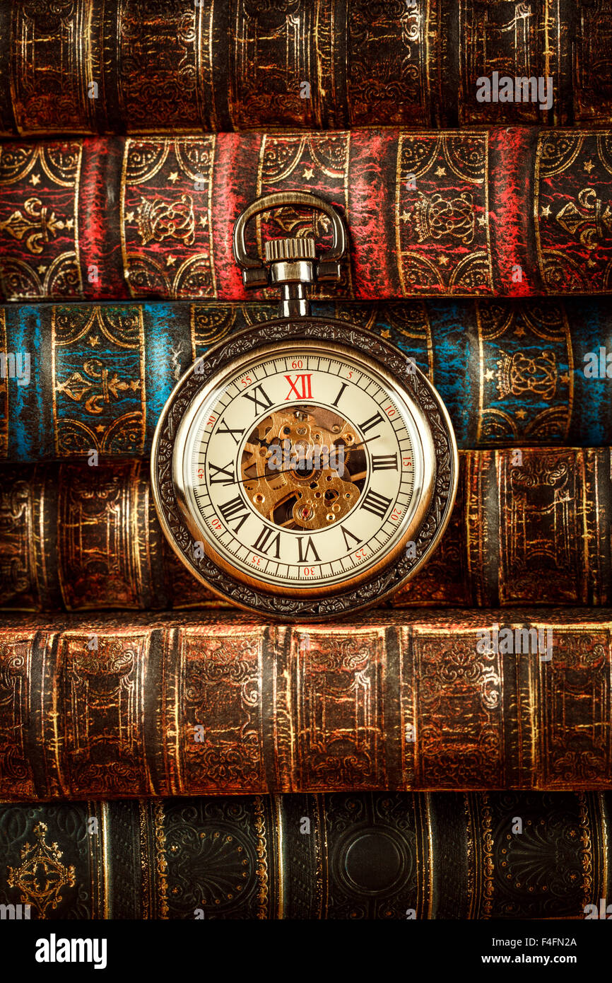 Vintage Antique pocket watch on the background of old books - Stock Image