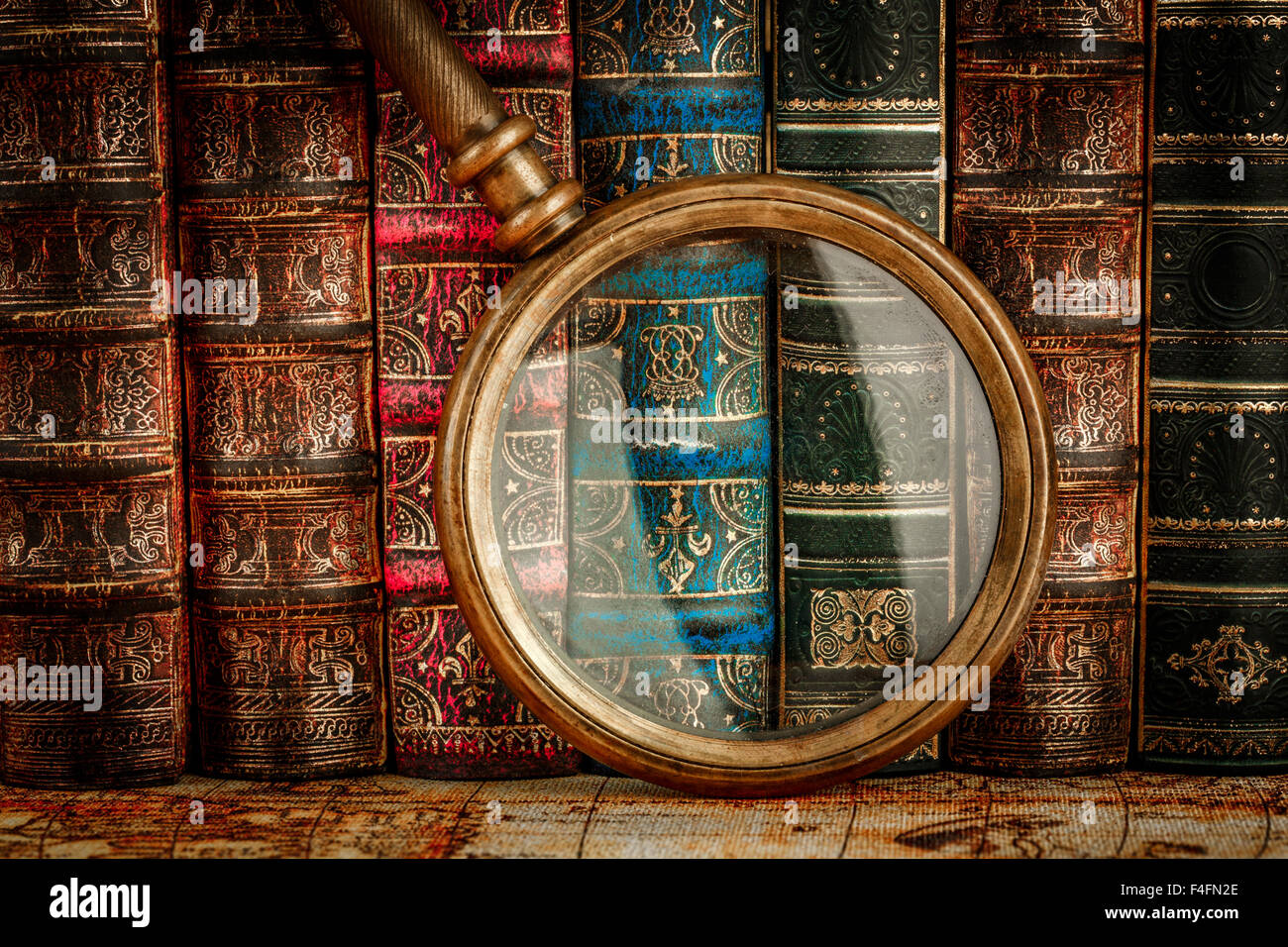 Ancient old books and magnifying glass - Stock Image