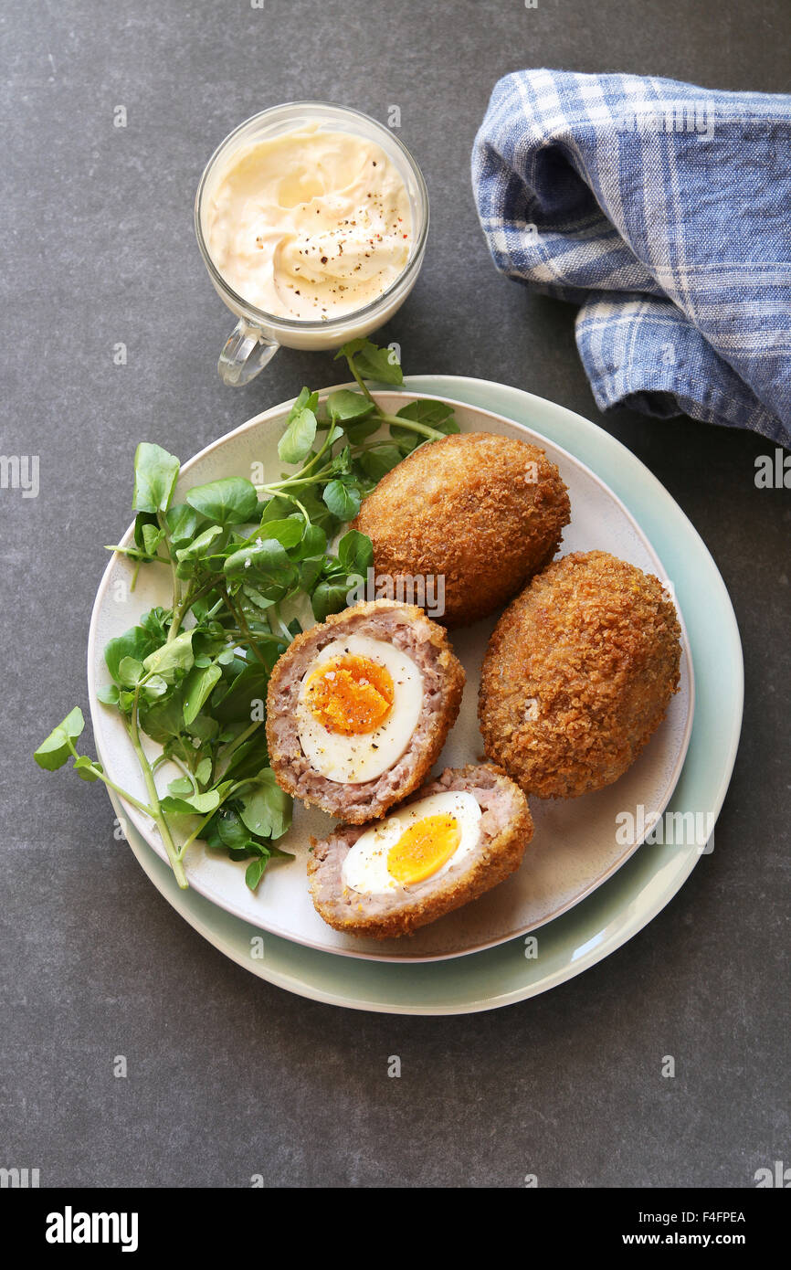 Scotch eggs on a plate with watercress salad and mayonnaise dip - Stock Image