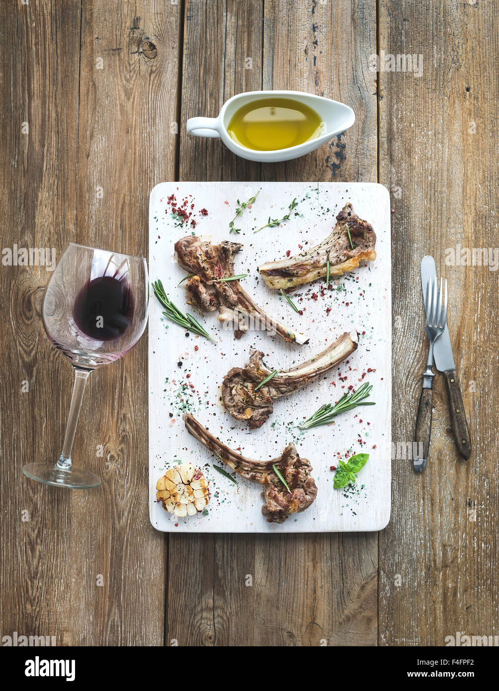 Grilled lamb chops. Rack of Lamb with garlic, rosemary and spices on white serving board, wine glass, oil in a saucer, - Stock Image