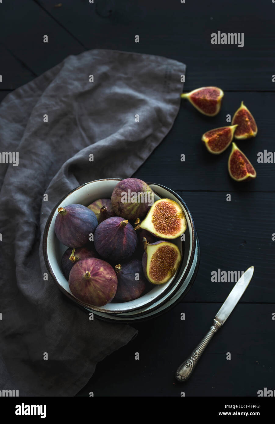 Rustic metal bowl of fresh figs on dark background, top view, selective focus Stock Photo