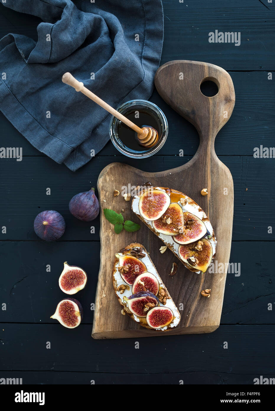 Sandwiches with ricotta, fresh figs, walnuts and honey on rustic wooden board over black backdrop, top view - Stock Image