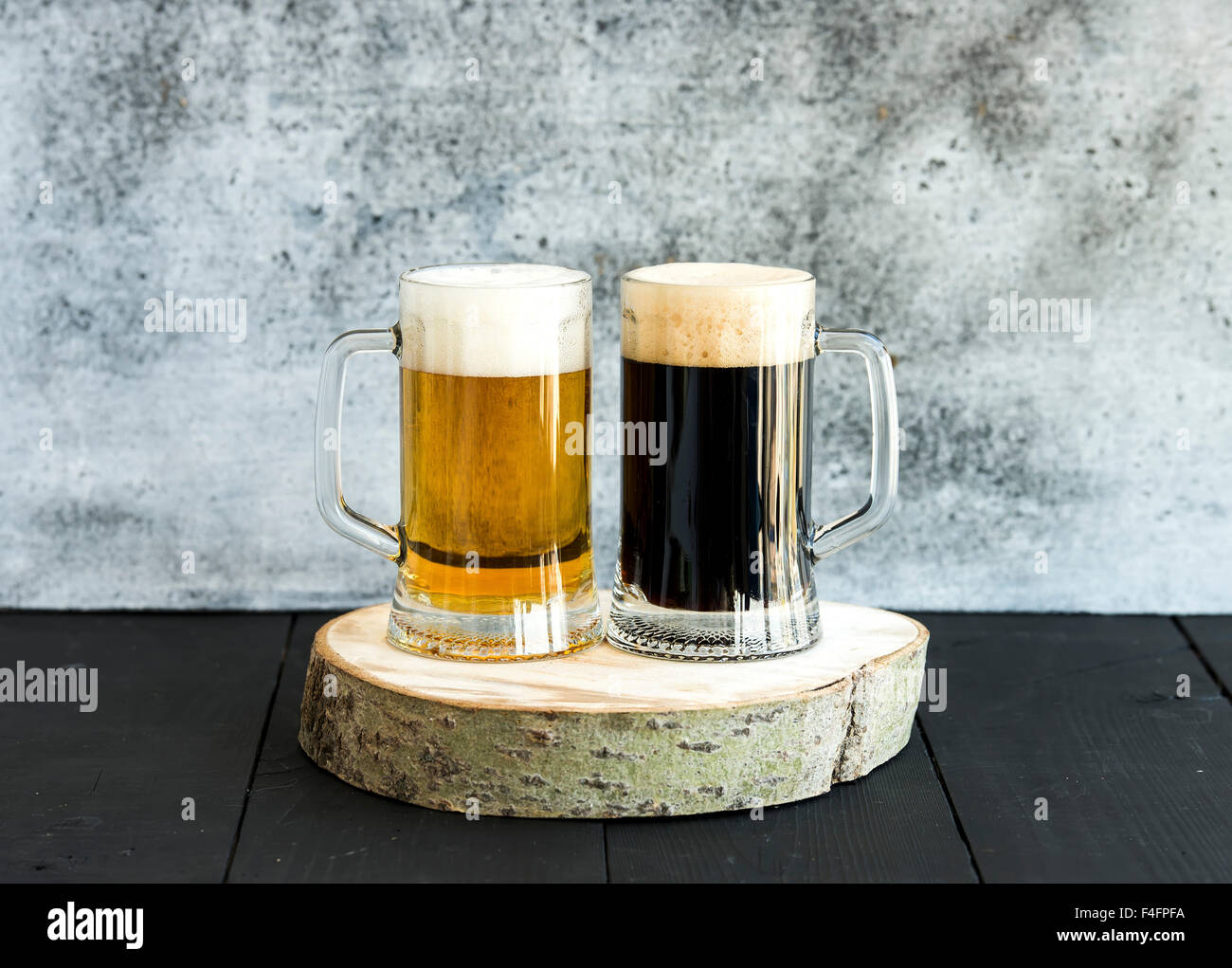 Light and dark beer in mugs on wooden board, grunge backdrop - Stock Image