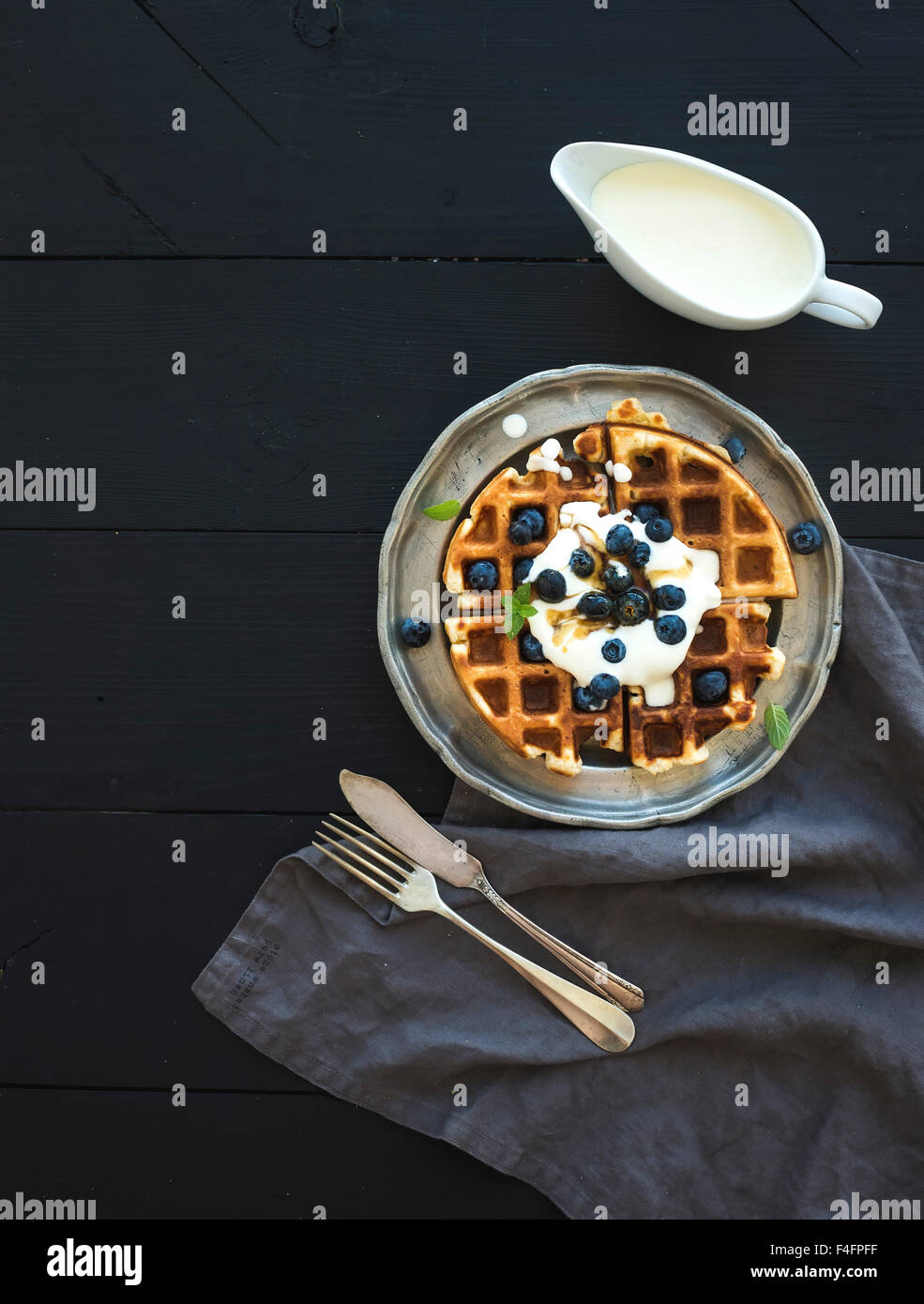 Soft Belgian waffles with blueberries, honey and whipped cream on vintage metal plate over black wooden background, - Stock Image