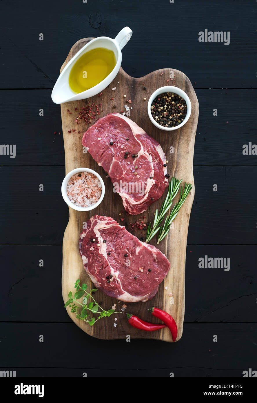 Raw fresh meat Ribeye steak entrecote and seasonings on cutting board on dark wooden background, top view Stock Photo