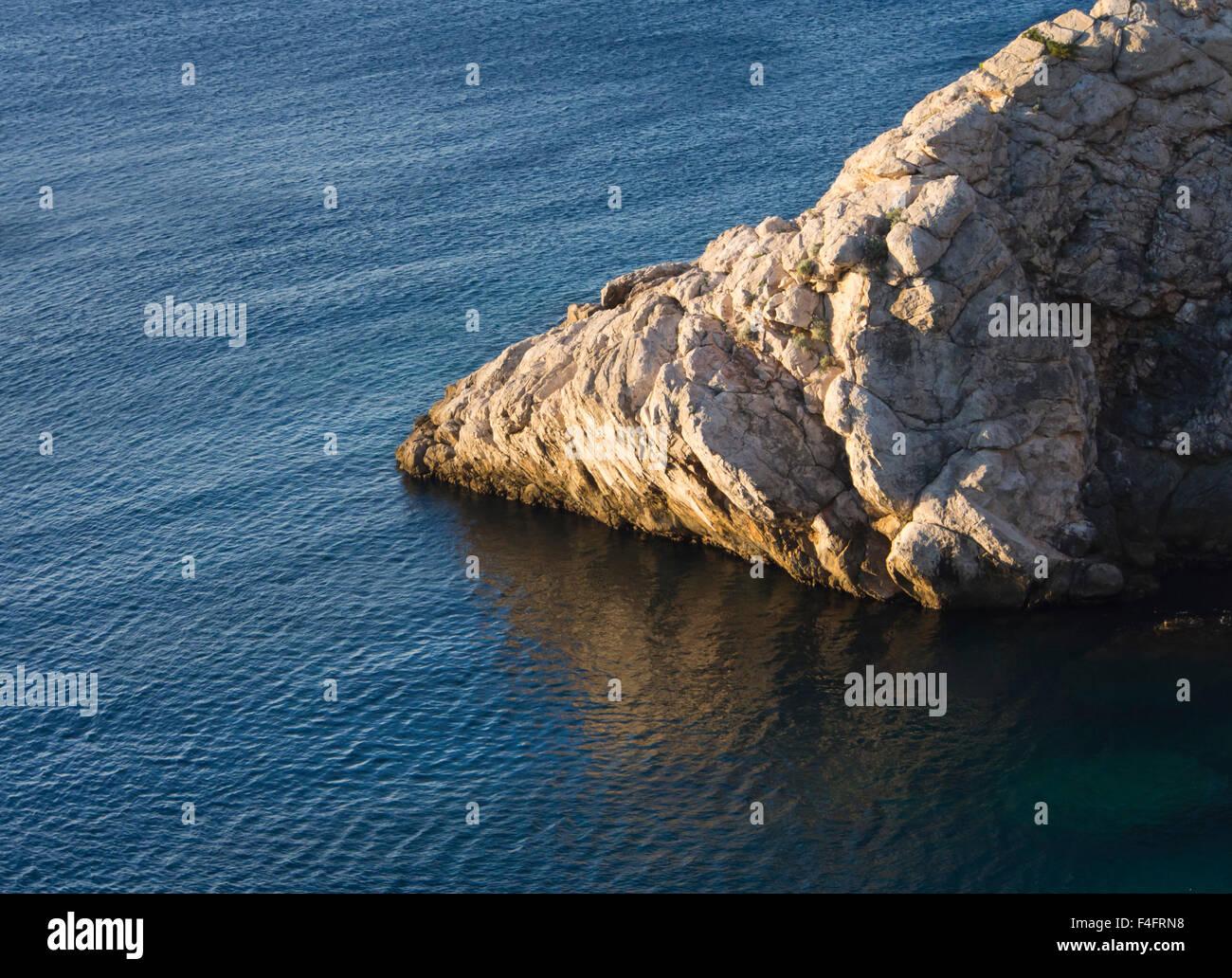 Cliff in yellow sunlight , blue sea, impression of the Dalmatian coast - Stock Image