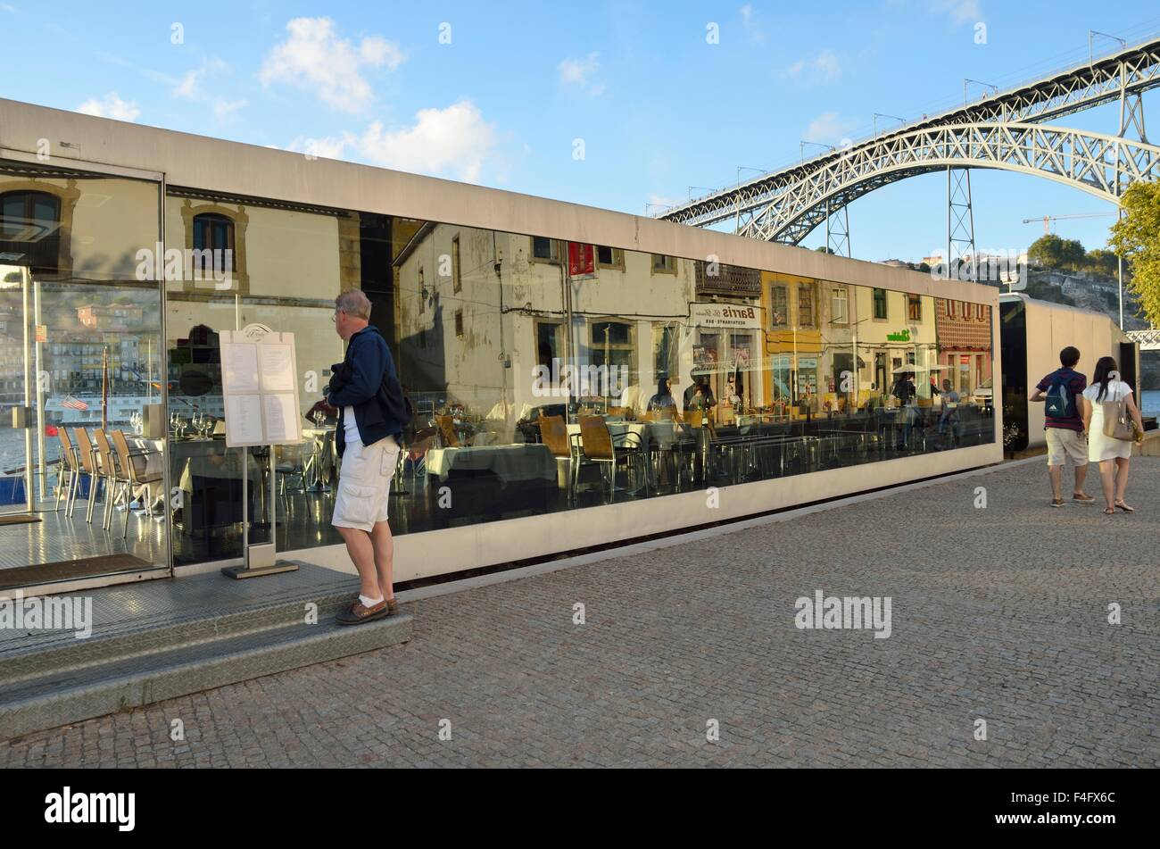 Reflections on crystal restaurant located in Gaia with the Don Luis Bridge at the end in Porto, Portugal. - Stock Image