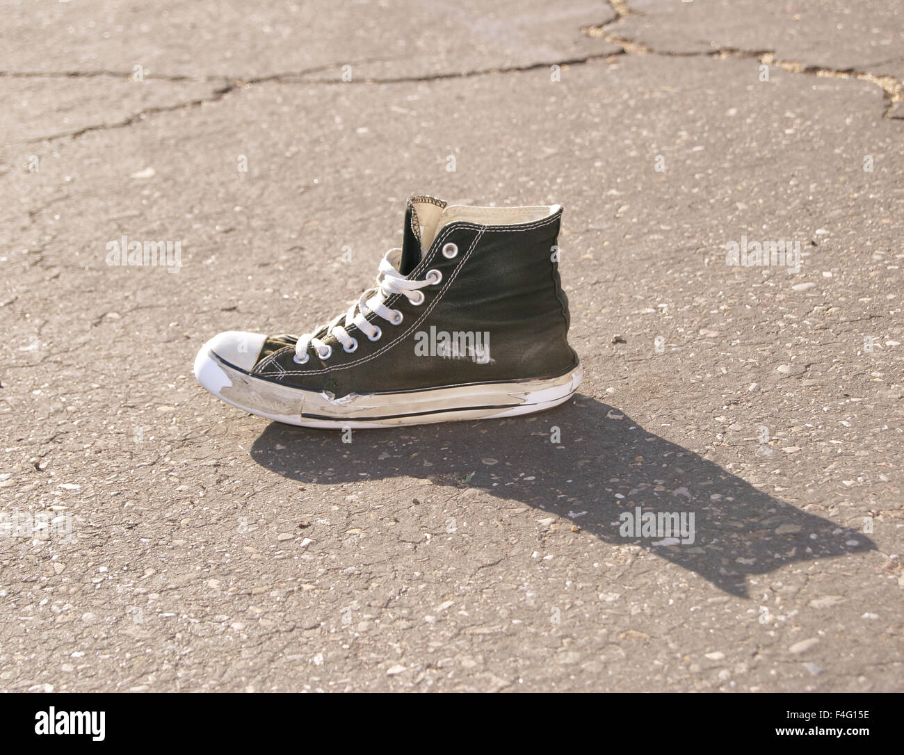 Worn out shoes on the concrete basketball court with setting sunlight and shadow. - Stock Image
