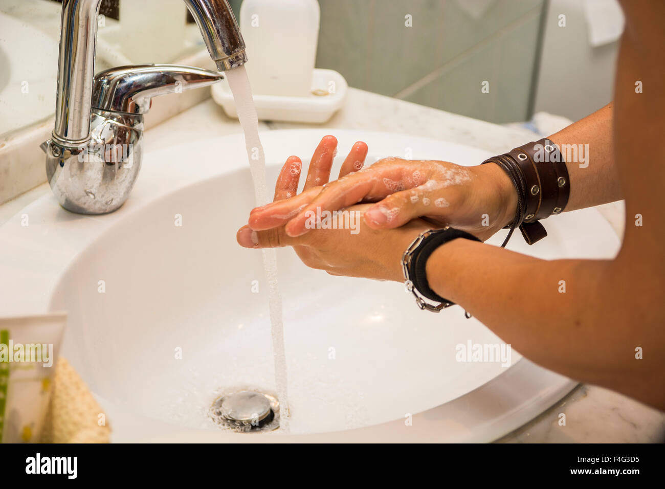 Young man's hands at bathroom washbasin using liquid soap for washing. - Stock Image