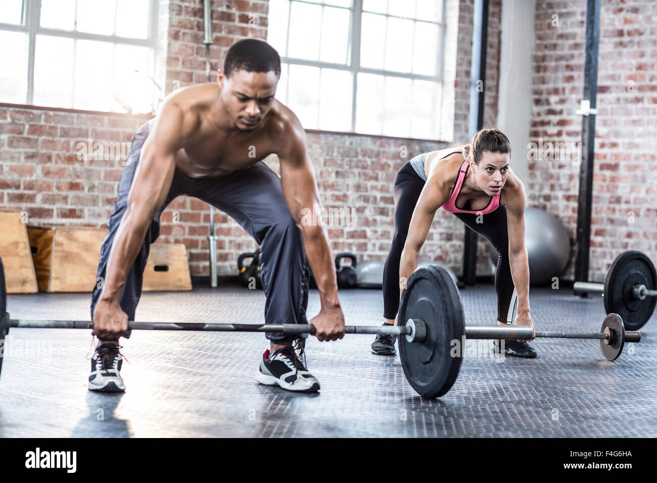 Fit couple lifting weight together - Stock Image
