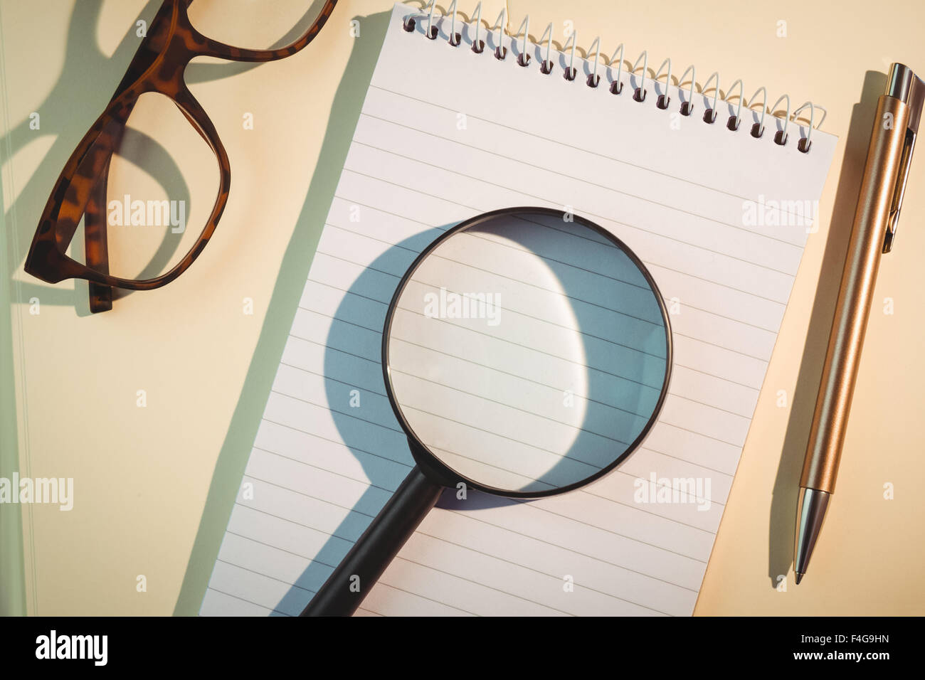Magnifying glass on notepad amidst pen and eyeglasses - Stock Image