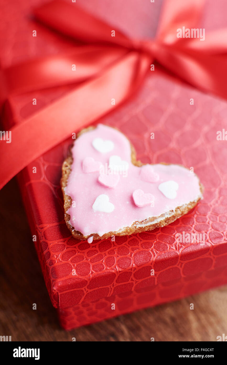 Heart shaped sugar cookie on a red gift box. Stock Photo