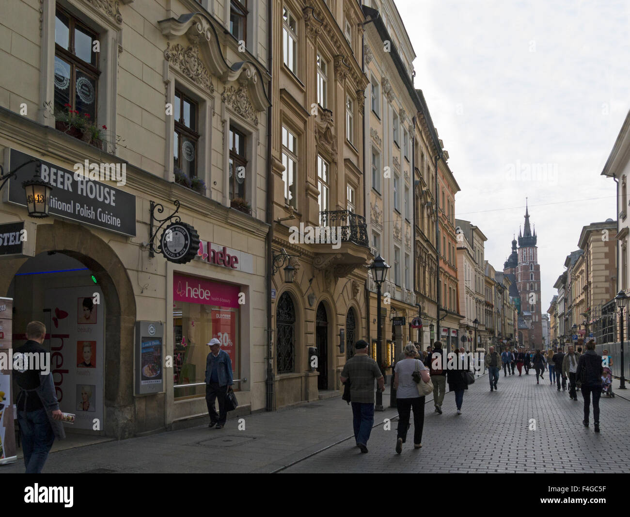 View down busy cobbled Florianska Street Krakow Poland to Bazylika Mariacka St Marys Basilica 14thc brick Gothic - Stock Image