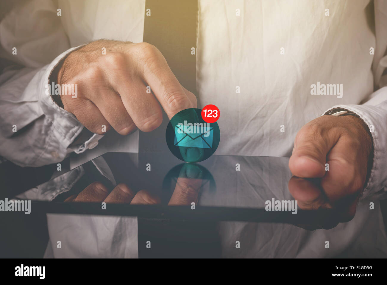 Businessman viewing e-mail messages on digital tablet computer, finger on touch screen of wireless device - Stock Image