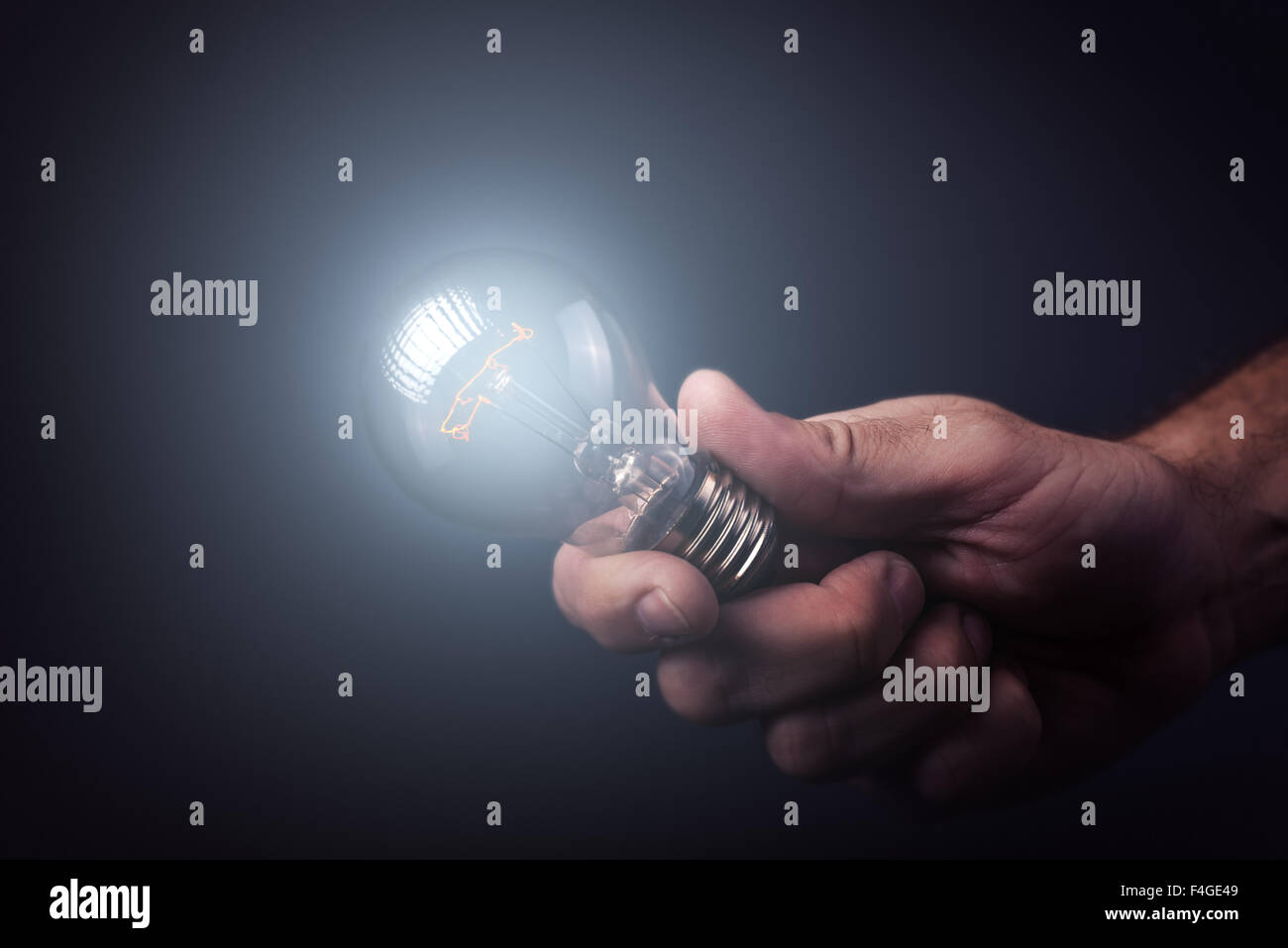 Creative enlightenment, understanding and generating new ideas, innovator and inventor with hand holding light bulb, - Stock Image