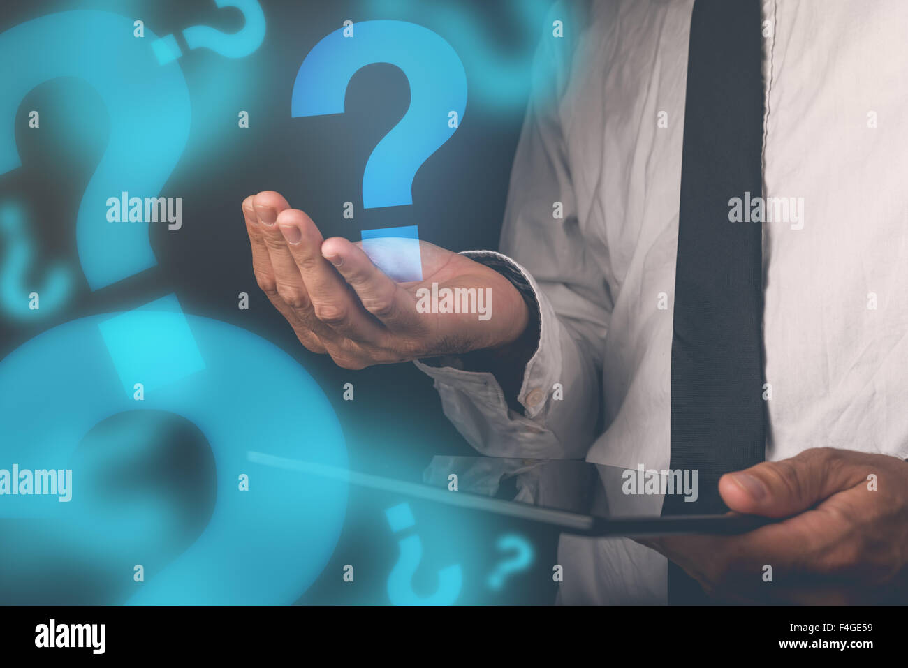 Businessman with questions, businessperson with digital tablet holding question mark, retro toned image, selective - Stock Image