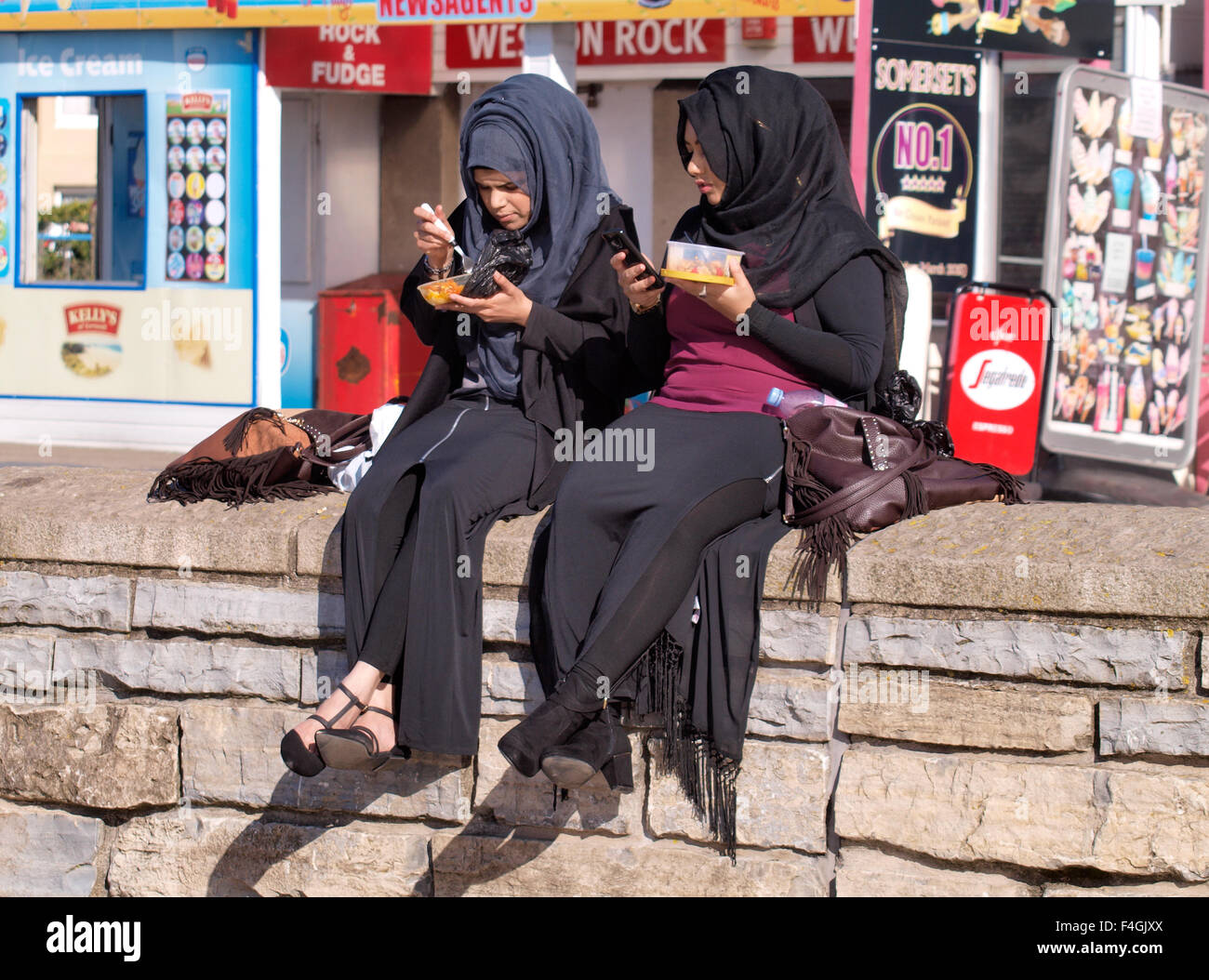 Two young Muslim women eating lunch, Weston-super-Mare, Somerset, UK - Stock Image